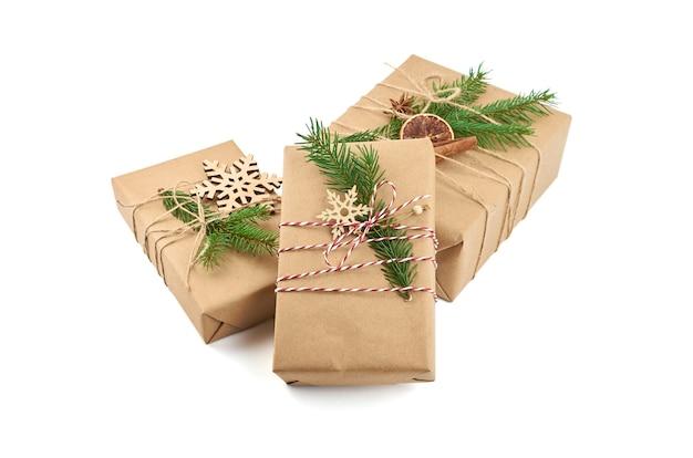 Trzy pudełka na prezenty świąteczne z świątecznymi dekoracjami i gałązką jodły