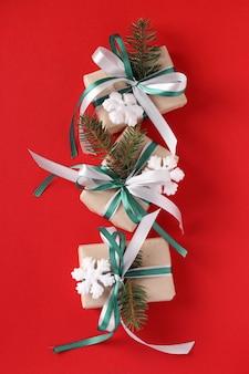 Trzy pudełka na prezenty świąteczne z zielono-białą wstążką na czerwonej powierzchni. widok z góry.