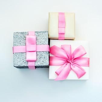 Trzy pudełka na prezenty wakacje związane z satynową tasiemką na różowym tle.