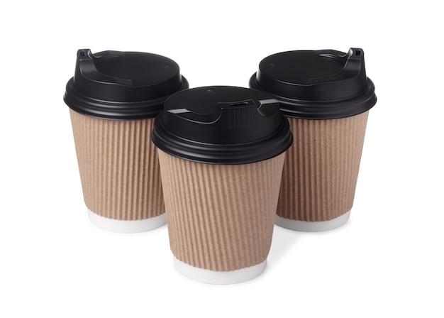Trzy puste papierowe kubki do kawy na wynos z czarnymi czapkami na białym tle.