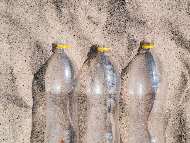 Trzy puste plastikowe butelki układają się w rzędzie na piasku