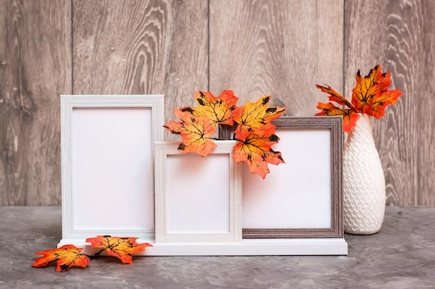 Trzy puste ramki na stojaku i wazon z pomarańczowymi liśćmi klonu stoją na stole. kolorystyka biało-pomarańczowo-beżowa. skopiuj miejsce