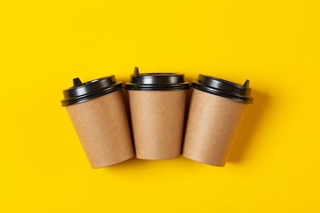 Trzy puste szare papierowe kubki z plastikową czarną pokrywką