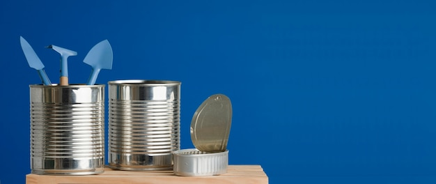 Trzy puszki z recyklingu na niebieskim tle drewnianego stołu