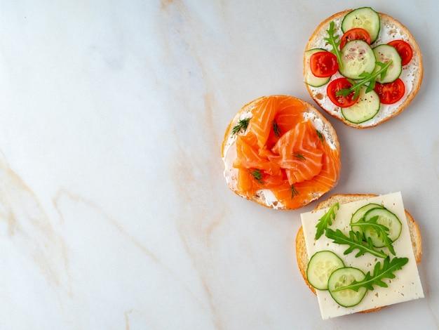 Trzy pyszne otwarte kanapki z łososiem, pomidorami, ogórkiem