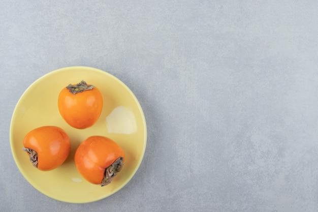 Trzy pyszne persimmons na żółtym talerzu