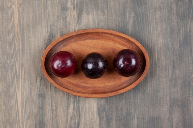 Trzy pyszne śliwki na drewnianym talerzu. wysokiej jakości zdjęcie