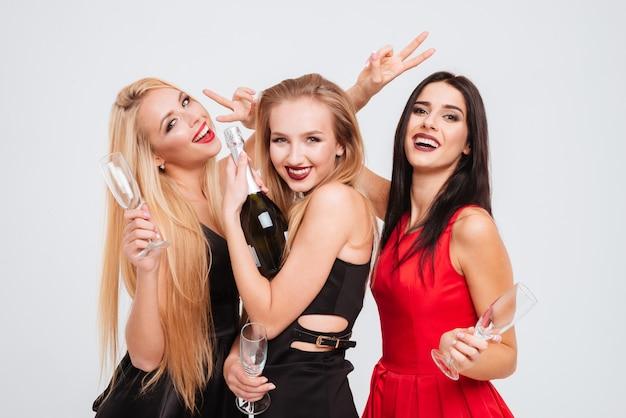 Trzy radosne, urocze młode kobiety piją szampana i bawią się razem na białym tle