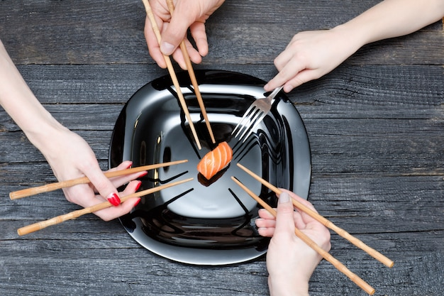 Trzy ręce pałeczkami, jedna z widelcem i sushi.