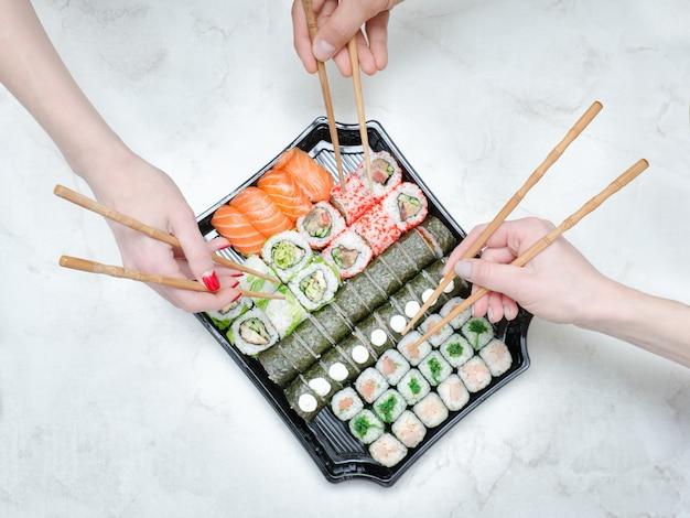 Trzy ręce z pałeczkami i zestaw sushi. widok z góry
