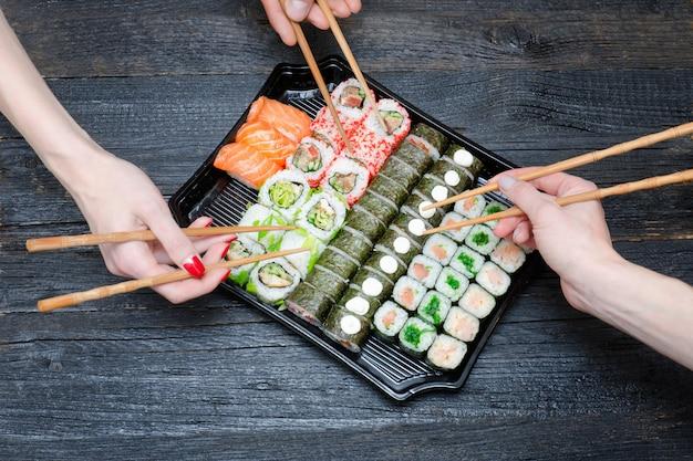 Trzy ręce z pałeczkami i zestaw sushi.