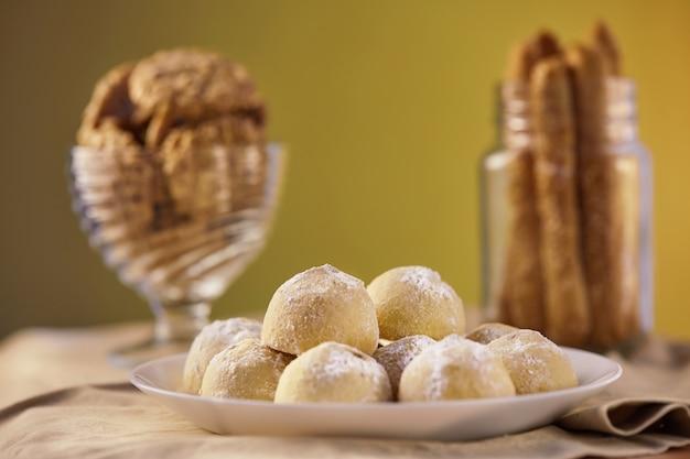 Trzy rodzaje ciasteczek w odcieniach beżu na serwetce w talerzu i słoiku. koncepcja stylu rustykalnego