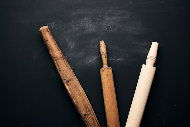 Trzy rodzaje drewnianych wałków do walcowania ciasta na czarnym tle