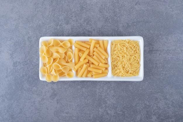 Trzy rodzaje niegotowanego makaronu na białym talerzu.