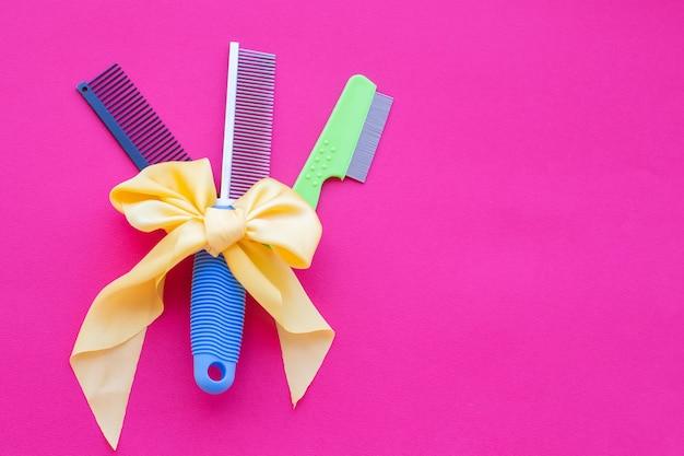Trzy rodzaje nożyczek fryzjerskich z żółtą kokardką na różowym tle.