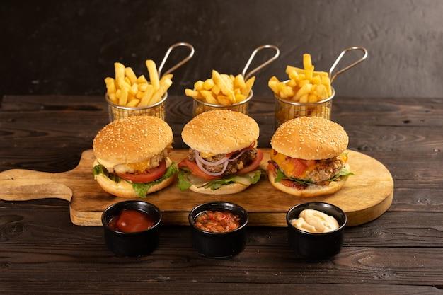 Trzy rodzaje soczystych burgerów wieprzowych, wołowych i drobiowych z frytkami i różnymi sosami pięknie zakonserwowane na ciemnym drewnianym stole.