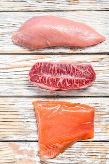 Trzy rodzaje steków na drewnianym stole. ostrze wołowe, filet z łososia i pierś indyka. ekologiczne mięso rybne, drobiowe i wołowe. białe tło. widok z góry.