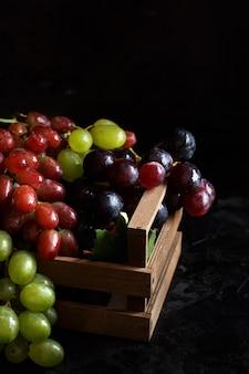 Trzy rodzaje winogron na ciemnym tle
