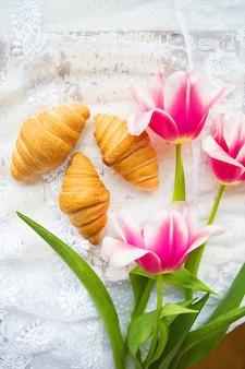 Trzy rogaliki i jasne różowe tulipany na koronkowym obrusie