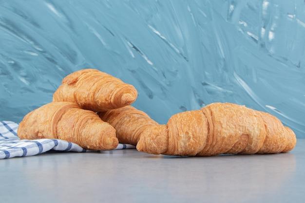 Trzy rogaliki ułożone na ręczniku z rogalikiem na marmurowym tle. wysokiej jakości zdjęcie