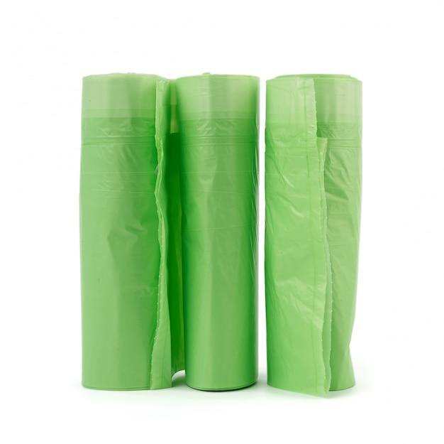 Trzy rolki z zielonymi plastikowymi torbami na śmieci na białym tle
