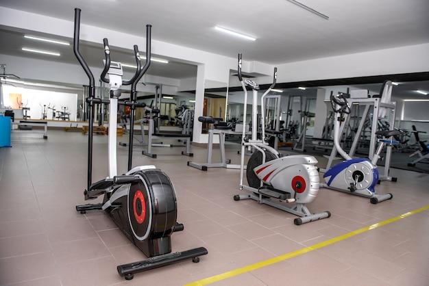 Trzy rowery treningowe na siłowni.