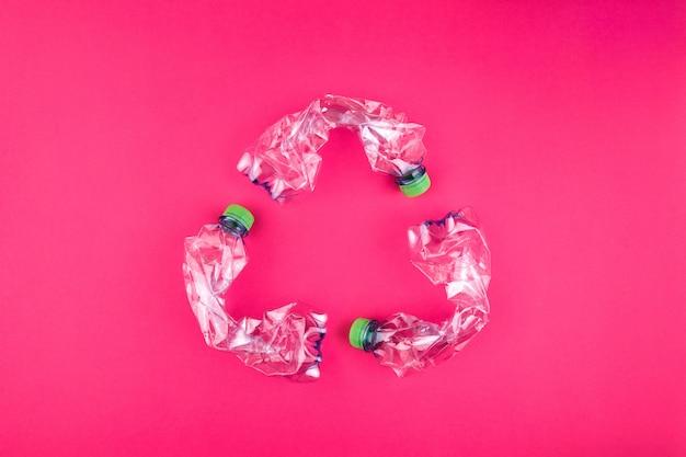 Trzy rozbite plastikowe butelki na jasnym różowym tle tworzą znak recyklingu