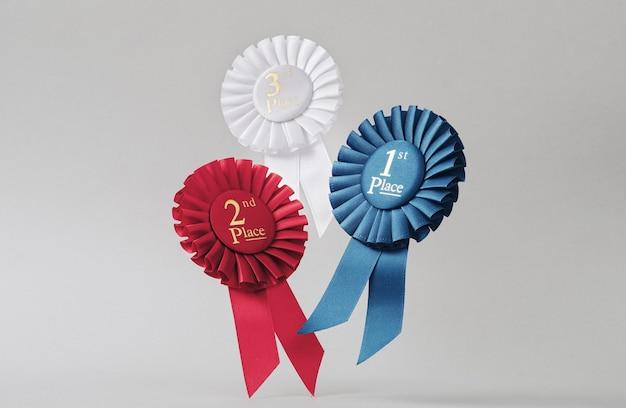 Trzy rozetki lecą na szarym tle jako nagrody dla zwycięzców i mistrzów za sukces i zwycięstwo.