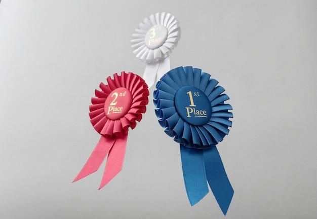 Trzy rozety lecą nad szarym tłem jako nagrody dla zwycięzców i mistrzów f