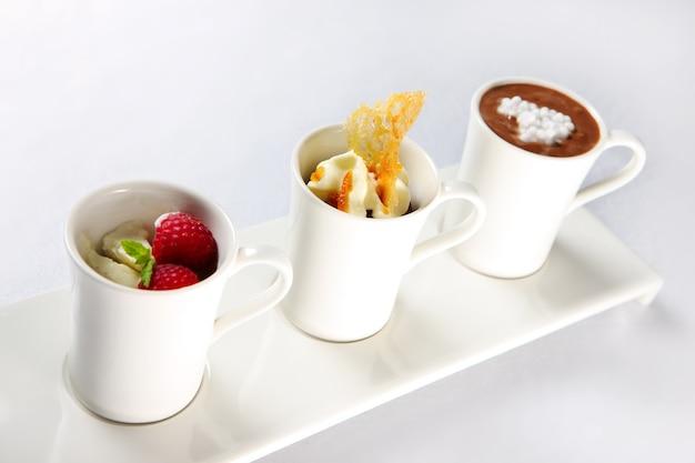 Trzy różne desery w kubkach na białym tle