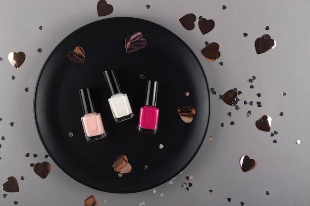 Trzy różne kolory lakieru do paznokci na czarnym talerzu wśród konfetti w kształcie serca
