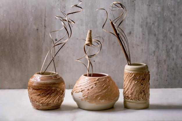 Trzy różne kształty beżowo-brązowych ceramicznych wazonów z suchymi kwiatami i gałązkami rozgałęziają się na białym marmurowym stole z szarą ścianą z tyłu. skopiuj miejsce.