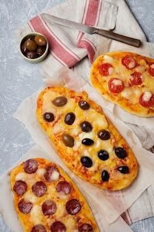 Trzy różne owalne pizze z oliwkami, pomidorem i salami na szarym betonie.
