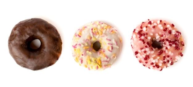 Trzy różne pączki z czekoladą i cukierkami w proszku na białym tle. widok z góry.