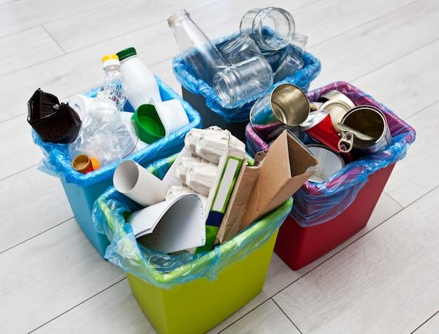 Trzy różne pełne pojemniki do sortowania śmieci.
