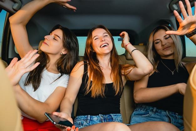 Trzy różne piękne koleżanki siedzą na tylnym siedzeniu pojazdu, słuchają piosenek muzycznych, śpiewają i tańczą