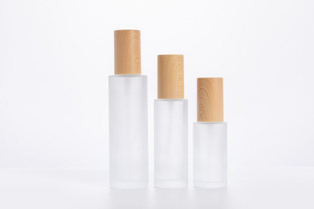 Trzy różnej wielkości butelki do pielęgnacji skóry na białej powierzchni