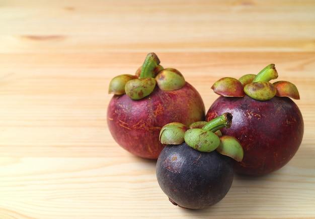 Trzy różnej wielkości i koloru dojrzałe purpurowe owoce mangostanu na drewnianym stole