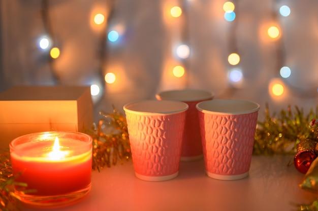 Trzy różowe kubki na bożonarodzeniowym tle z płonącymi świeczkami i świecącą girlandą w kolorze pomarańczowym. mała głębia ostrości.