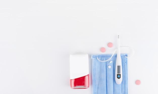 Trzy różowe pigułki, elektroniczny termometr, spray na kaszel, niebieska maska medyczna na białym tle. leżał płasko, kopia przestrzeń. pojęcie medycyny sezonowa choroba grypa, wirus, katar, temperatura