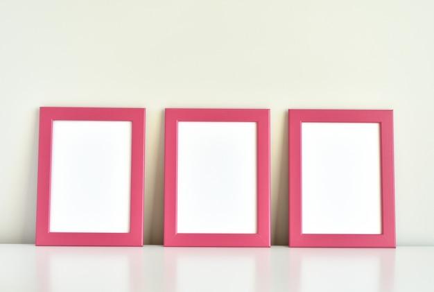Trzy różowe ramki na białym stole.