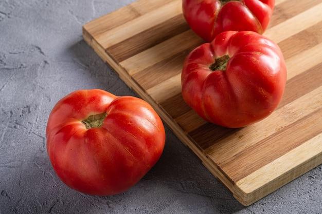 Trzy różowe rodzynkowe warzywa pomidorowe, świeże czerwone dojrzałe pomidory na drewnianej desce do krojenia, wegańskie jedzenie, tło z betonu kamiennego, kąt widzenia