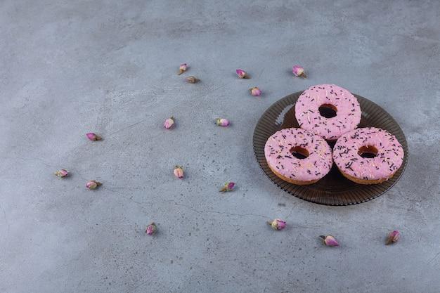 Trzy różowe słodkie pączki z kwitnącymi różami na szklanym talerzu.