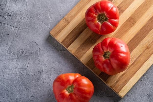 Trzy różowego heirloom pomidorowego warzywa, świezi czerwoni dojrzali pomidory na drewnianej tnącej desce, weganinu jedzenie, kamienia betonowy tło, odgórny widok