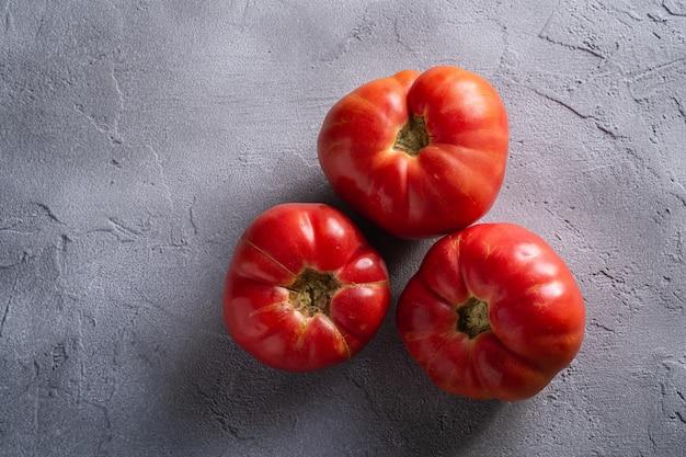 Trzy różowego heirloom pomidorowego warzywa, świezi czerwoni dojrzali pomidory, weganinu jedzenie, kamienia betonowy tło, odgórny widok