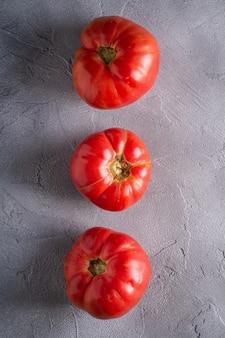 Trzy różowego heirloom pomidorowego warzywa w rzędzie, świezi czerwoni dojrzali pomidory, weganinu jedzenie, kamienia betonowy tło, odgórny widok
