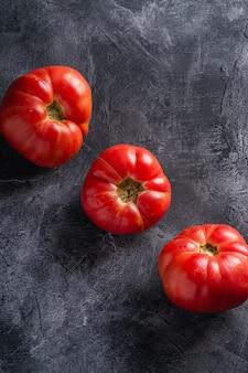 Trzy różowego heirloom pomidorowego warzywa w rzędzie, świezi czerwoni dojrzali pomidory, weganinu jedzenie, zmroku kamienia betonu tło, kąta widok