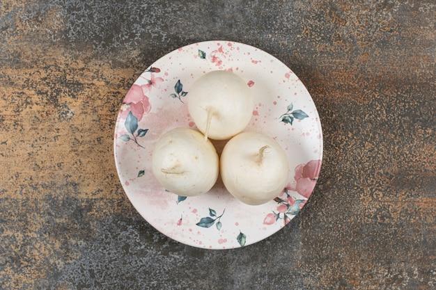 Trzy rzodkiewki na talerzu, na marmurowej powierzchni