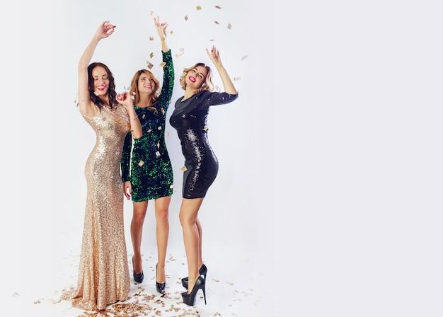 Trzy seksowne kobiety w luksusowych brokatowych cekinach ubierają się, tańcząc i bawiąc się. makijaż hollywood, falująca fryzura. białe tło. pełna wysokość.