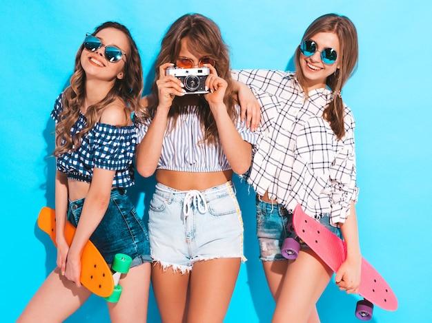 Trzy seksowne piękne stylowe uśmiechnięte dziewczyny z kolorowymi deskorolkami grosza. kobiety w lecie pozowanie ubrania kraciaste koszule. modele robiące zdjęcia aparatem fotograficznym retro